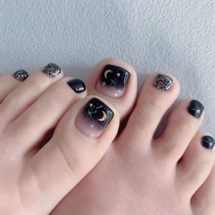 Pedicure in black and nude colors with details of stars and golden moons