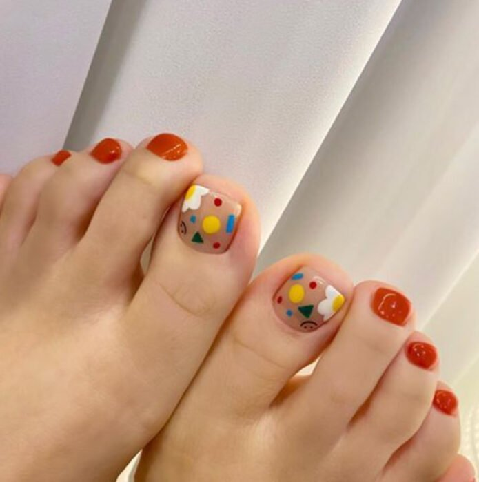Pedicure in orange and blue, yellow and white colors
