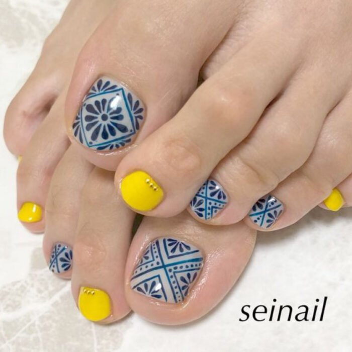Pedicure in yellow and blue colors with mosaic design