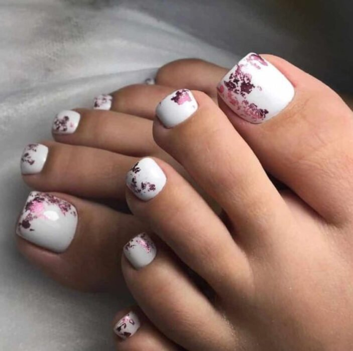 Pedicure in white with details in wine and cherry color