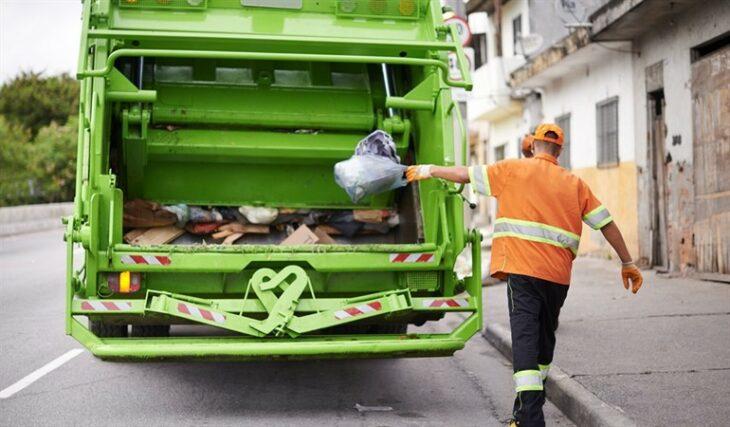 Recolector de basura colocando una bolsa de desechos en el camión de basura