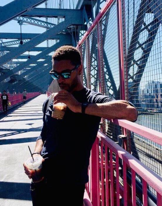 Actor Regé-Jean Page tomando un café en un puente