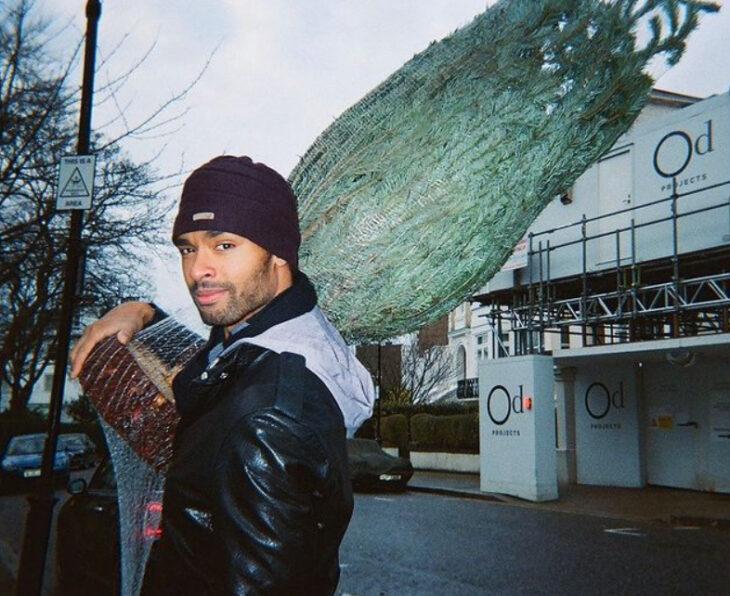 Actor Regé-Jean Page cargando un árbol de Navidad