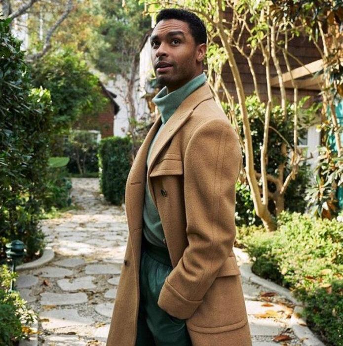 Actor Regé-Jean Page usando un suéter verde y abrigo camel