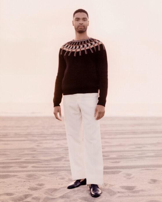 Actor Regé-Jean Page usando pantalón blanco y suéter guinda