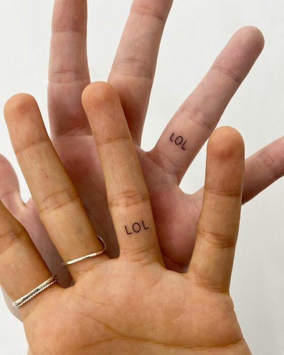 """Tatuaje de palabra """"lol"""" en el dedo anular"""