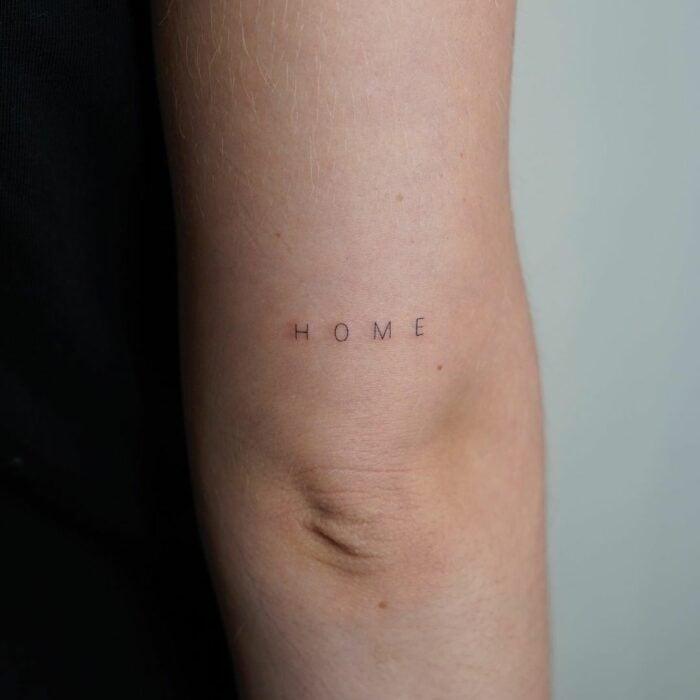 "Tatuaje de palabra ""home"" arriba del codo"