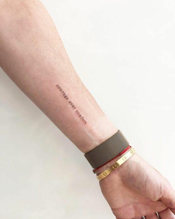 """Tatuaje de """"courage over comfort"""" en el brazo"""