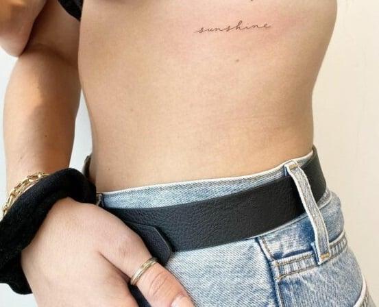 Tatuaje de frase en inglés en la costilla para chicas