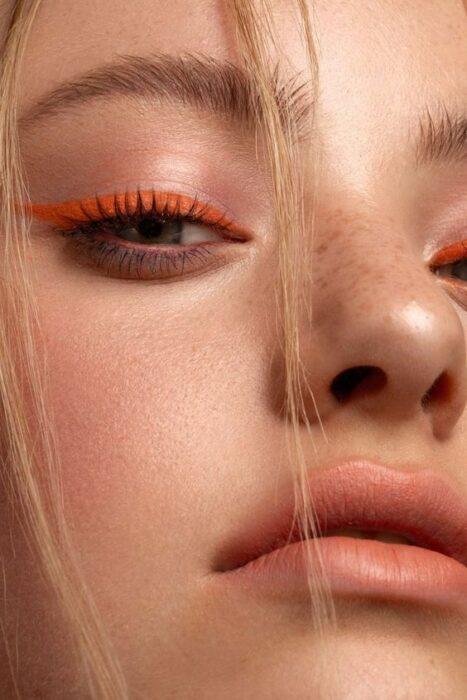 Chica de cabello rubio con delineado color naranja