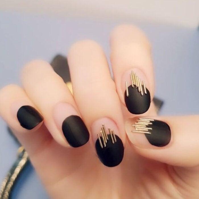 Manicura con diseño de color negro y líneas doradas