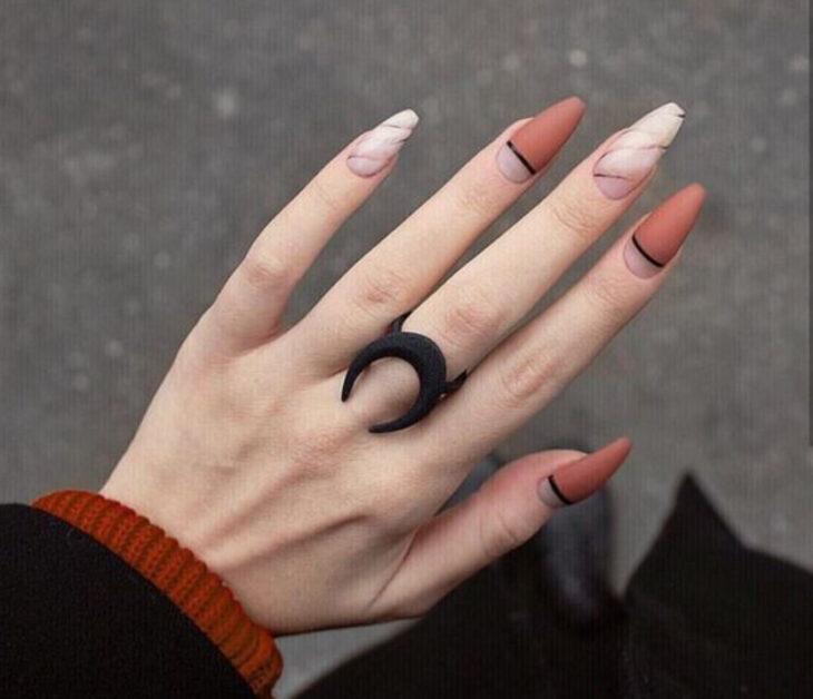 Manicura con diseño de marmol, líneas y colores naranja quemado y nudes