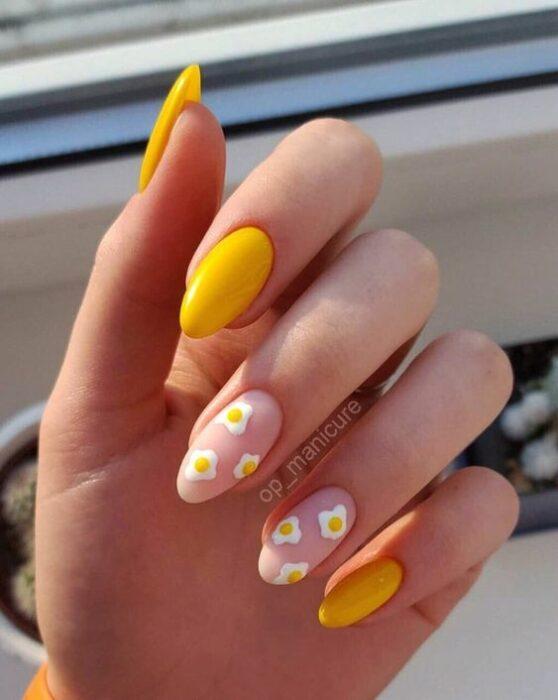 Chica con manicura stiletto en color amarillo con efecto mate