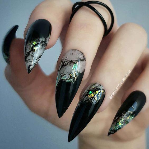 Chica con manicura stiletto en color negro con estampado metalizado