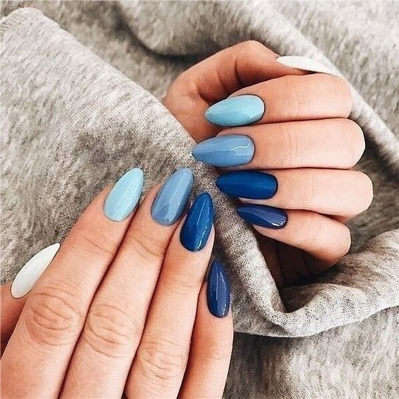 Girl with stiletto manicure in blue colors