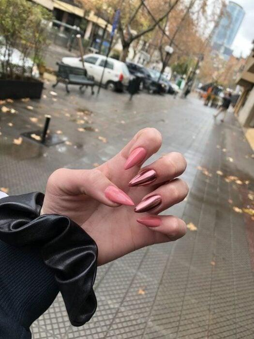 Chica con manicura stiletto en color rosa con efecto metálico