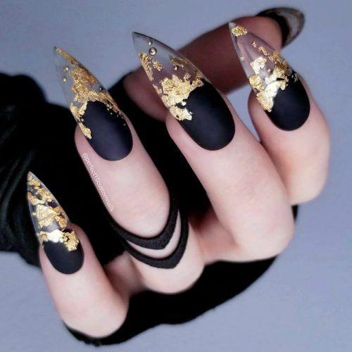 Chica con manicura stiletto en color negro con puntas doradas