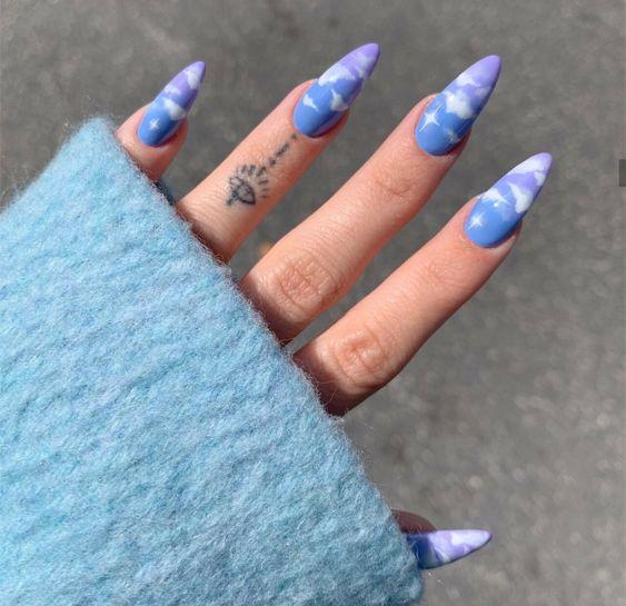 Chica con manicura stiletto en color azul cielo con diseño de nubes blancas