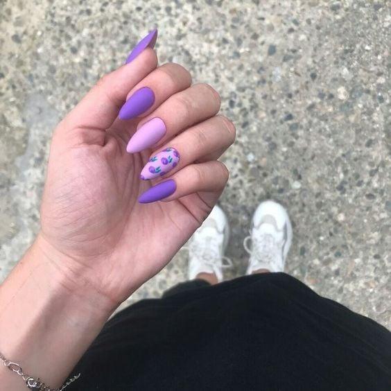 Chica con manicura stiletto en color lila con efecto mate