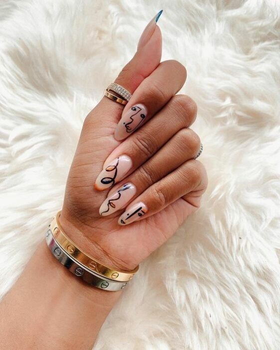 Girl with stiletto manicure in nude color decorated with paintings