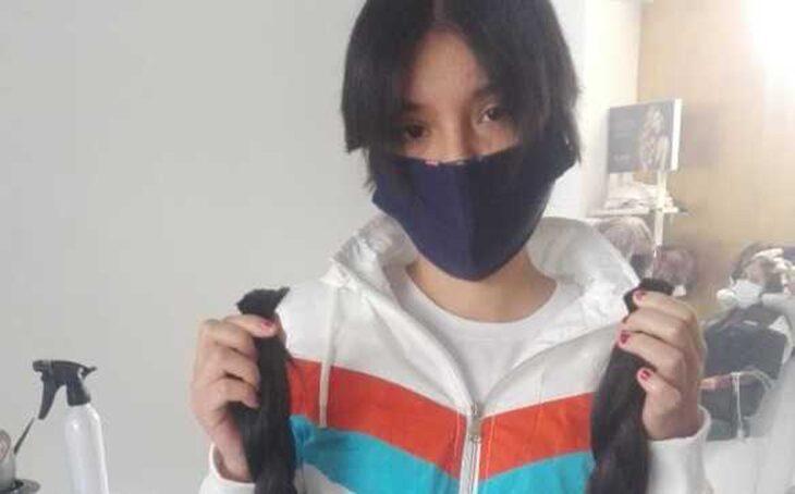 Chica sosteniendo su propio cabello cortado entre las manos; Vendió su cabello para comprarle un tanque de oxígeno a su abuelito