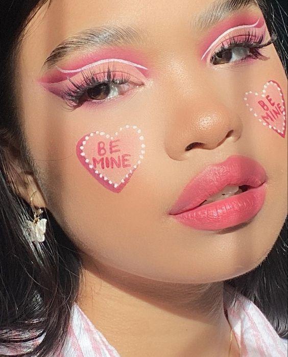 Chica con maquillaje rosa y corazones en las mejillas;