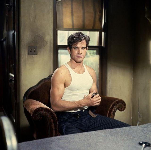 Warren Beatty sentado en un sofá
