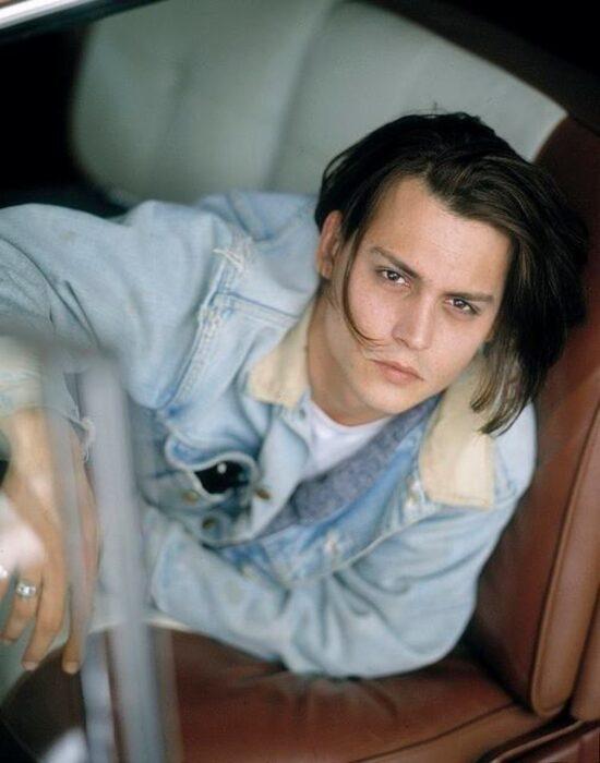 Johnny Depp posando para una fotografía dentro de un auto