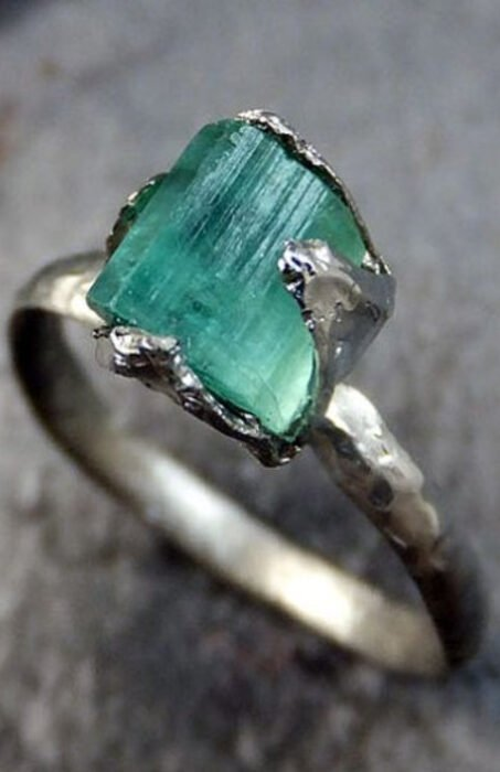 Silver-colored engagement ring with blue-green stone