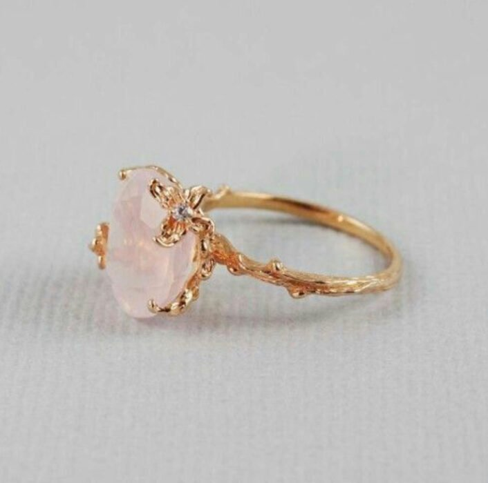 Gold color engagement ring with pink stone