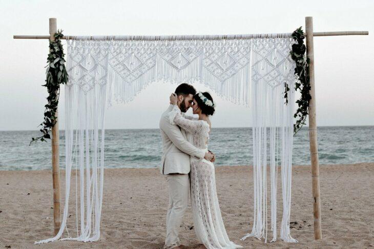Pareja de novios casándose en la playa con el mar de fondo