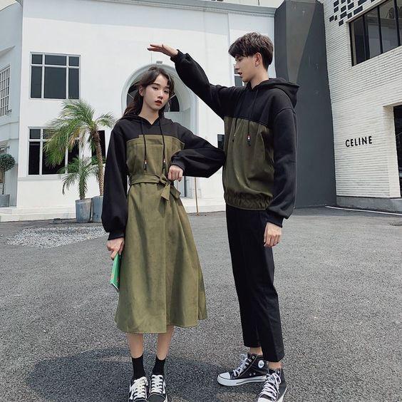 Pareja coreana posando en la calle ella con un vestido largo color verde militar y una sudadera negra y él con una conjuntos deportivo negro con converse negros