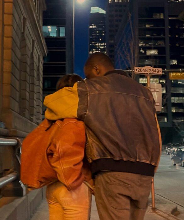 Pareja de espaldas caminan por la calle el usa chamarra café de piel mientras abraza por encima de los hombros a sui novia que viste una chaqueta color marrón