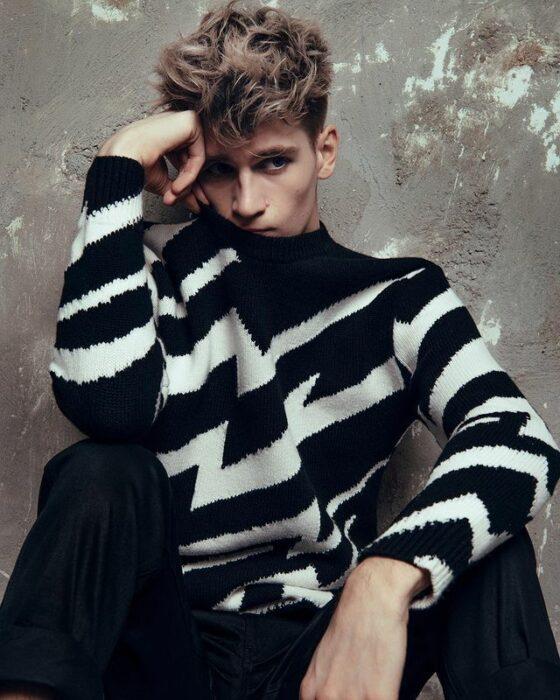 Danny Griffin sentado en el piso con un suéter a rayas en blanco y negro