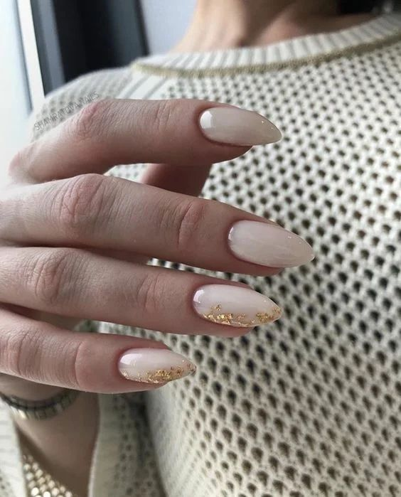 White almond tip nails with gold edge accents