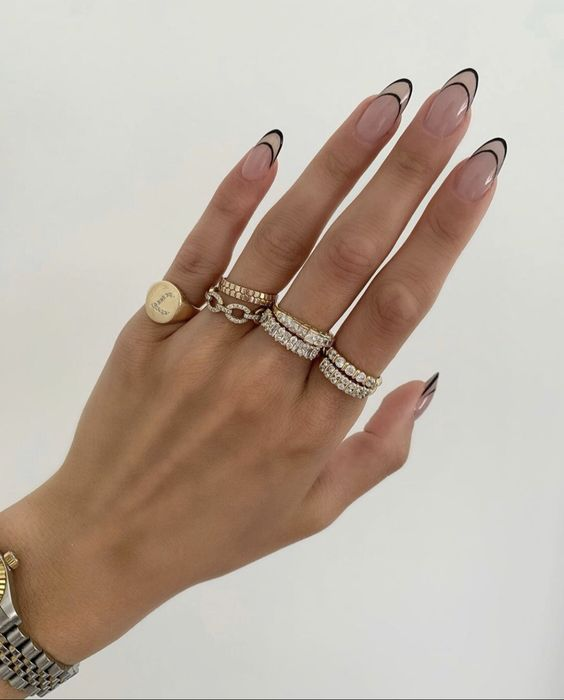 Slim hand with rings on each finger and long almond shaped nails with tips decorated with black lines