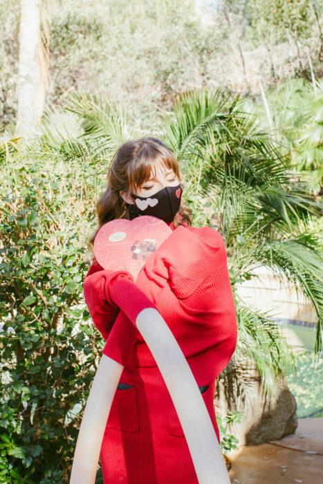 chica abrazando un corazón de cartón;  fotografía de Alexa Machado