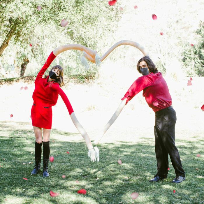 Pareja formando un corazón con brazos gigantes; fotografía de Alexa Machado