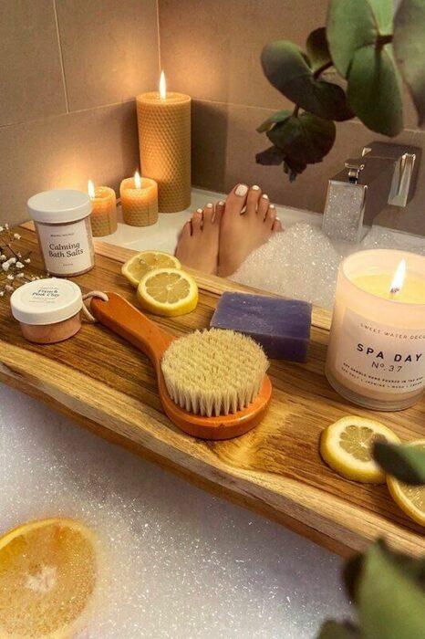 Chica en una bañera llena de espuma con una tabla que sostiene una vela y cosas para spa