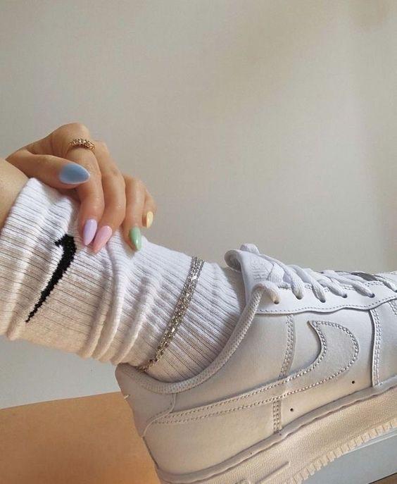 pies de chica con calcetas y tenis blancos posando sus uñas de colores pastel