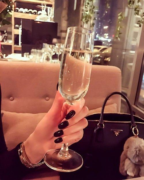 Mano de mujer con uñas acrílicas pintadas de negro sosteniendo una copa de champaña