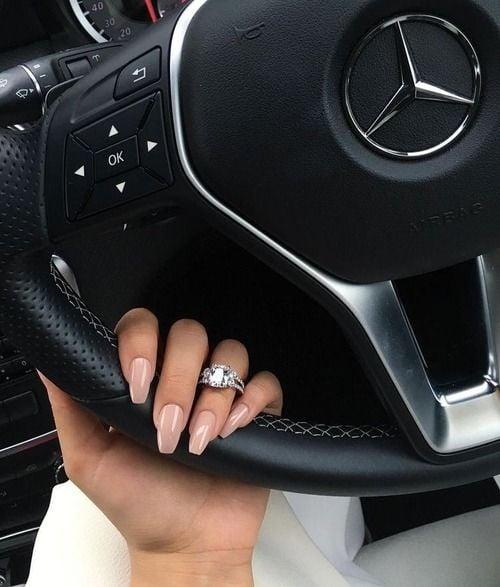 Mano de mujer con uñas acrílicas color rosa con un anillo en el dedo anular y sujetando el volante de un auto