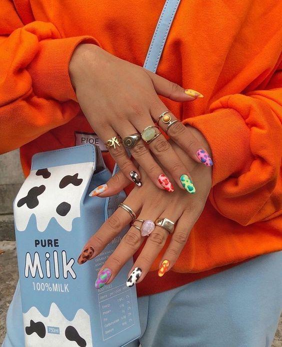 Chica con sudadera larga color naranja posando con la manos enfrente llena de anillos en cada dedo