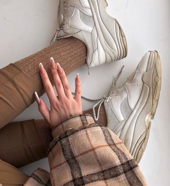 Chica sentada en el piso con outfit café con beige y mano con uñas color beige