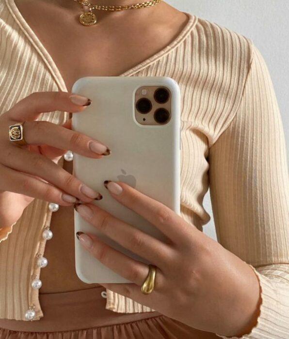 Chica tomándose selfie con iPhone sujetándolo con uñas con punta de animal print