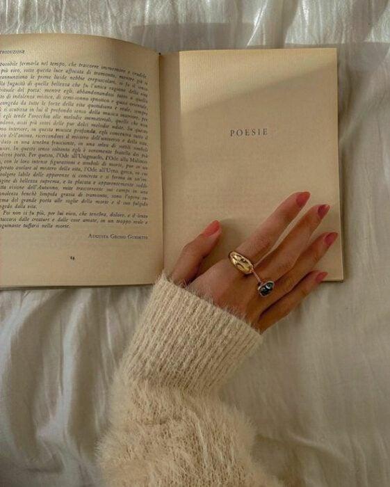 Chica apoyando su manos con las uñas pintadas de rosa sobre un libro con páginas antiguas