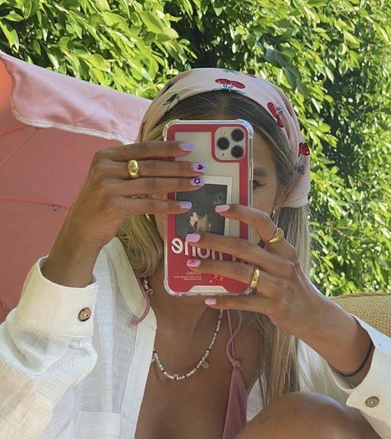 Chica rubia tomándose selfie tapando su rostro  y usando un pañuelo con estampado de cereza en la cabeza