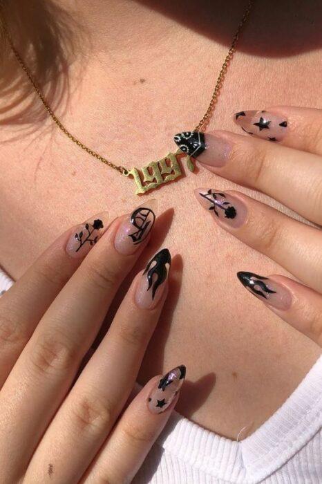 Chica usando cadena dorada con número 1997 apoyando sus uñas acrílicas largas con detalles negros