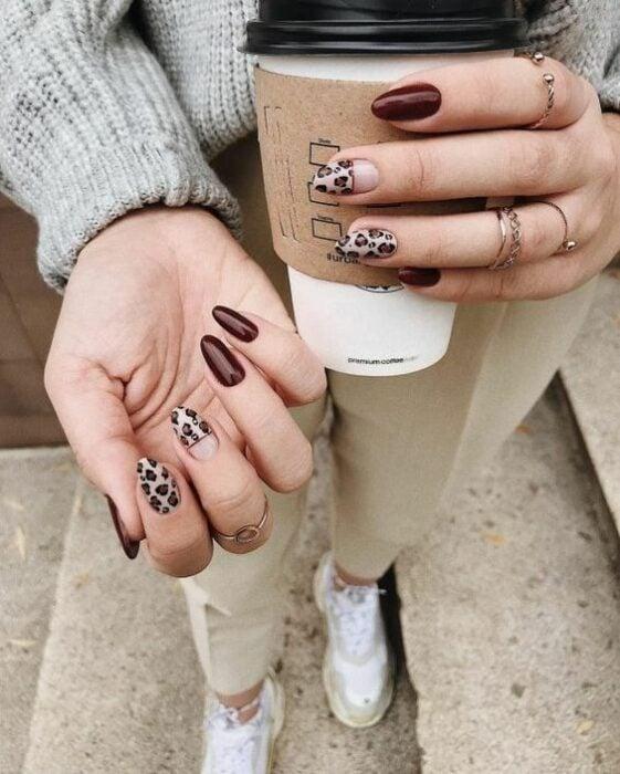 Chica sosteniendo un vaso de café y mostrando sus uñas color vino y beige con detalles de leopardo
