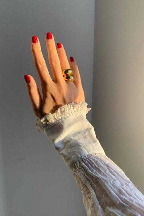 Mano de una mujer posando en el sol con las uñas pintadas de rojo y un anillo grande dorado